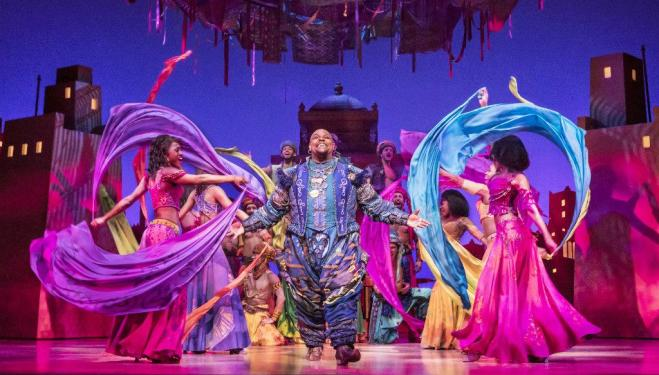 Genie (Trevor Dion Nicholas) in market surrounded by scarfs - photo by Johan Persson © Disney.jpg